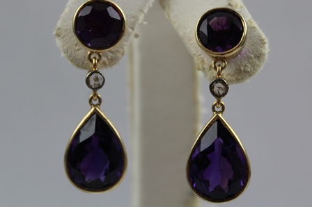 A PAIR OF 14CT GOLD AMETHYST AND DIAMOND DROP EARRINGS, each having circular amethyst with small diamond above a pear drop shaped amethyst, on butterfly fitting