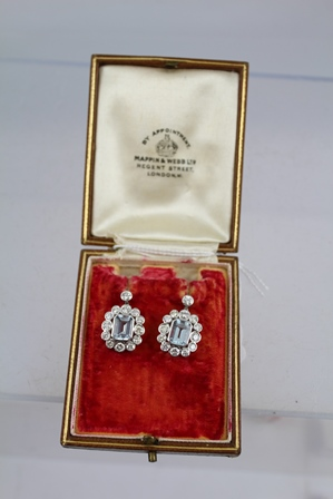 A PAIR OF AQUAMARINE AND DIAMOND CLUSTER DROP EARRINGS, each set with a rectangular emerald cut aquamarine surrounded by twelve graduated diamonds with single diamond above, on butterfly fitting