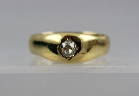 AN 18CT GOLD AND DIAMOND SOLITAIRE UNISEX RING, set with a single half carat diamond in gypsy style setting, on a substantial shank, size X