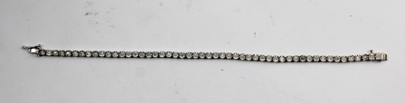 A RHODIUM FINISHED WHITE GOLD AND DIAMOND BRACELET, having fifty-one diamonds in claw setting, and push clasp with safety catch