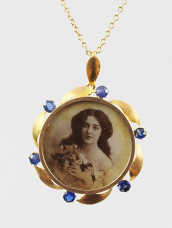 A GOLD COLOURED METAL LOCKET PENDANT, bordered with six sapphires interspersed with plain stylised leaf scroll, on chain