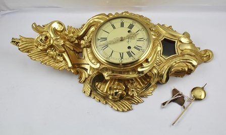 A ROCOCO DESIGN CARVED GILT WOOD CARTEL CLOCK, the dial with Roman numerals, inscribed Standard Stockholm, dial 16cm, overall 65cm high