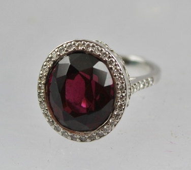 A RHODIUM FINISHED WHITE GOLD COLOURED METAL RUBELLITE AND DIAMOND CLUSTER RING, comprising large rubellite surrounded by numerous small diamonds, with diamond shoulders, size O tight