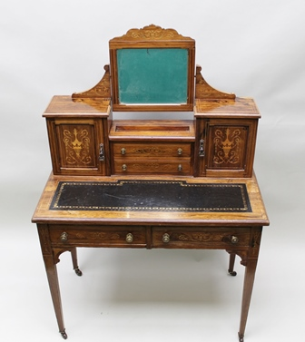 AN EDWARDIAN ROSEWOOD BONHEUR DU JOUR WRITING DESK, having marquetry inlaid urn decoration, fitted bevel mirror over a superstructure of cupboards and drawers, with tooled leather writing surface over two frieze drawers, raised on squared tapering supports with castors, 92cm wide