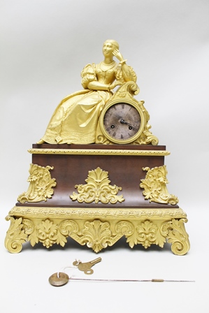 A FRENCH EMPIRE ORMOLU MANTEL CLOCK, cast with a  reclining lady wearing 17th century costume, silvered dial and Roman numerals, 8-day striking movement on silk suspension, the base cast with acanthus leaf feet, 46.5cm high