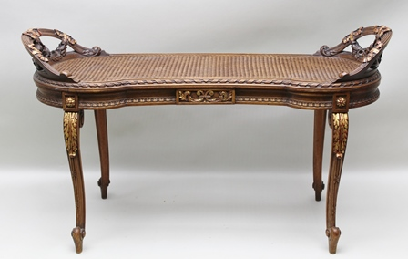 A FRENCH EMPIRE DESIGN DUET SEAT, carved bound reeded and floral swags parcel gilt, woven cane bergere panel seat, raised on cabriole supports, 108cm wide