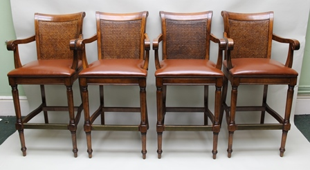 A SET OF FOUR WALNUT OPEN ARM BAR STOOLS, each having woven cane bergere panelled back, scroll arms and leather seat, raised on turned fore supports with plain stretchers and  brass mounted foot rail