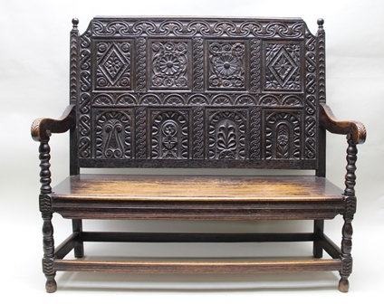 A 17TH CENTURY DESIGN OAK SETTLE incorporating early timbers, having carved panel back, open arms, panelled seat, on turned fore supports with stretchers, 131cm wide x 125cm high
