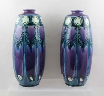 A PAIR OF MINTON SECCIONIST DESIGN CERAMIC VASES, tube lined and painted with swags in blue/green on lavender ground, factory stamp to bases Minton Ltd No.1, 32cm high