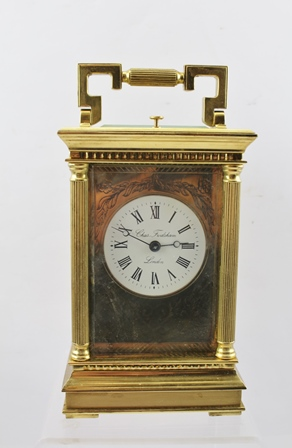 A 20TH CENTURY CHARLES FRODSHAM BRASS REPEATING CARRIAGE CLOCK, having white enamel dial with Roman numerals, engraved face plate, the case of classical architectural column form, fitted carrying handle, eight day movement, the back plate engraved Charles Frodsham, London, case 16cm high (excluding handle)