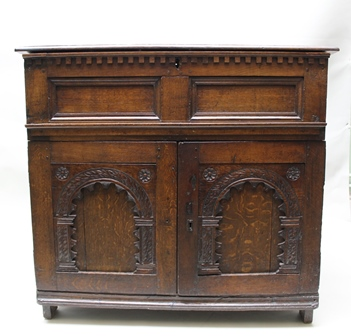 A PART LATE 17TH CENTURY OAK CABINET, the top fitted hinged lid, opening to reveal a storage compartment with later pigeon holes, over dentil cornice and two plain panels, over base fitted two cupboard doors with arched panel decoration, raised on stile end supports, panelled sides and planked back, 102cm wide x 63cm deep x 95cm high