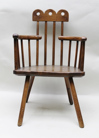 A 19TH CENTURY PRIMITIVE DESIGN CHILDS WINDSOR CHAIR, having pierced tri-lobed crest, raised on four spars, curved arms and a demi-lune seat, raised on staked legs, English c.1850