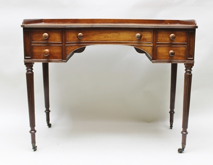 A 19TH CENTURY MAHOGANY DRESSING OR WRITING TABLE having gallery back, concave centre, fitted five drawers with knob handles, raised on fluted supports and castors, 103cm wide
