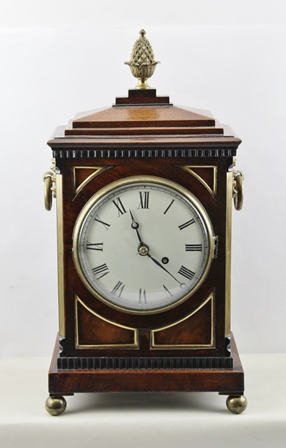 A LATE GEORGIAN/EARLY VICTORIAN REGENCY STYLE MAHOGANY BRACKET TIMEPIECE, having stepped pediment, later finial and flank brass handles with grill panel sides, English line fusee drive, faced by a Roman enumerated circular dial, raised on brass ballfeet, 46cm high x 23cm extreme