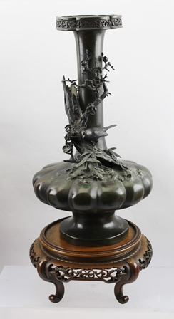 A JAPANESE MEIJI PERIOD BRONZE VASE, having elongated flared neck upon a squat lobed gourd body, outswept circular platform base, the body decorated with cast bird perched amidst blossom and thorn branch, incised character marks to base, 36cm high, raised upon a polished wood stand with pierced frieze on four scroll feet
