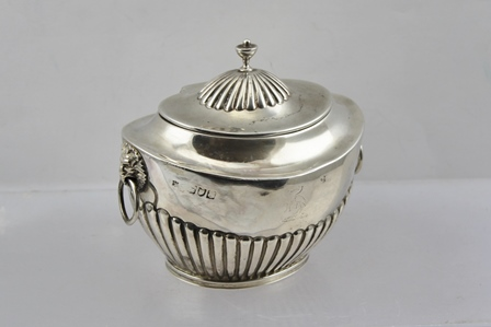 GOLDSMITHS AND SILVERSMITHS COMPANY WILLIAM GIBSON AND JOHN LAWRENCE LANGMAN A LATE 19TH CENTURY SILVER CADDY of oval form with fluted decoration, the hinged cover with knop, fitted lion mask ring handles, 10cm high, engraved with crane family crest, London 1899, 208g