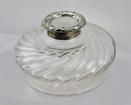 CORNELIUS JOSHUA VANDER A LATE 19TH CENTURY INKWELL, having clear glass reservoir with swirling decoration to the shoulders, fitted hinged silver cover, London 1893, 13cm diameter