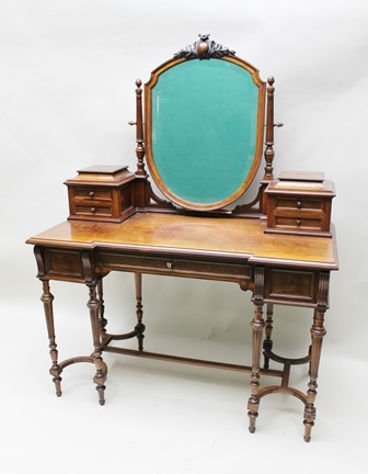 A LATE VICTORIAN ROSEWOOD DRESSING TABLE, having shield shape bevel plate mirror with carved crest, the top with two banks of trinket drawers, over a base fitted with three drawers on fine turned and fluted supports with plain stretches, 114cm wide