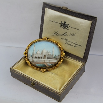 AN IMPRESSIVE YELLOW METAL FRAMED BROOCH, painted with a central panel of Shah Jahans, 17th century Taj Mahal, Mausoleum, the glazed back reveals a blue fabric panel, image 5cm x 6cm, in the vendors tooled leather, silk and velvet lined presentationbox inscribed Reville Ltd., 15 Hanover Square, London W. By Special Appointment to her Majesty the Queen, circa 1900