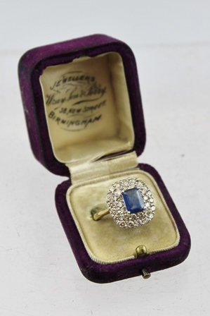 A SAPPHIRE AND DIAMOND RING, having central cushion cut sapphire (7mm x 5mm) surrounded by a double row of diamonds, on an 18ct gold band, size L 1/2