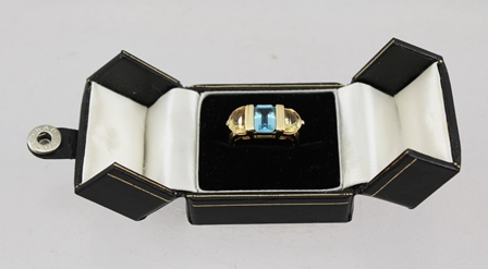 AN 18ct GOLD RING set with a central emerald cut blue topaz flanked by two citrines, size Q 1/2