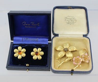 TWO 18CT GOLD FLORAL DESIGN BROOCHES, one set central sapphires, the other enamelled petals, together with a PAIR OF YELLOW METAL FLORAL DESIGN EARRINGS, in George Pragnell box