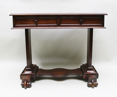 A 19TH CENTURY MAHOGANY WRITING OR SIDE TABLE having leather inset top over a frieze fitted two drawers with knob handles, raised on plain trestle ends with scroll feet and shaped stretcher, 94cm wide