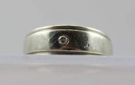 A GENTLEMANS 9ct WHITE GOLD RING with a solitaire diamond set in the gypsy style, size T, overall weight 5g.