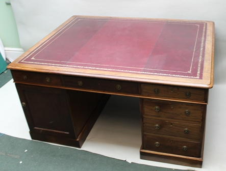A 19TH CENTURY MAHOGANY TWIN PEDESTAL PARTNERS DESK, the top inset with gilt tooled burgundy leather writing surface, fitted three frieze drawers to either side, the pedestals each fitted with three drawers, with decorative brass ring handles, 120cm x 153cm