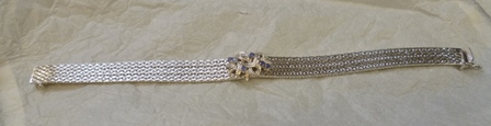 A RHODIUM FINISHED 18CT WHITE GOLD BRACELET, having plaited base set with a suite of six sapphires on a knot
