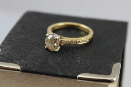 AN 18CT YELLOW GOLD ONE CARAT DIAMOND SOLITAIRE RING with diamond set shoulders, stamped 750, size M
