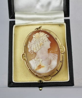 H** B** & S** A 9CT GOLD FRAMED CAMEO BROOCH/PENDANT, featuring a Grecian style lady with flowers in her hair wearing a string of beads around her neck, in a decorative pierced fretwork style mount with four curving double scrolls between, stamped 9ct