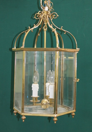 A 20TH CENTURY REGENCY DESIGN BRASS FRAMED HALL LANTERN of hexagonal form with bevelled glass panels, three lamp fittings, with suspension ring and chain, overall 57cm high