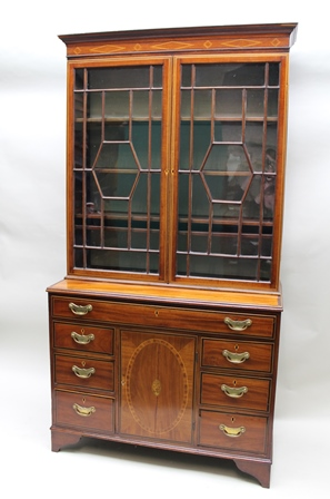 A 19TH CENTURY MAHOGANY SECRETAIRE BOOKCASE the top fitted astragal glazed doors, over base with secretaire drawer, having leather writing surface and small drawers over a base of six drawers fitted brass handles and flanking a central cupboard, on bracket feet, 109cm wide