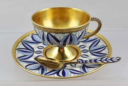 A RUSSIAN SILVER GILT CUP AND SAUCER WITH TEASPOON, wire work cloisonne decoration, in blue on white stylised leaf design, marked 916
