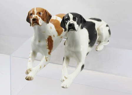 TWO USSR PORCELAIN MODELS OF POINTER DOGS, lying with forelegs outstretched, one black and white, the other orange and white, printed marks to base, 30cm long