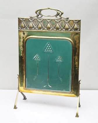 AN ARTS AND CRAFTS DESIGN BRASS FIRESCREEN IN THE MANNER OF VOYSEY, the top with cast tendril handle, embossed crest of floral motifs over an etched bevel mirror inset, overall height 81.5cm