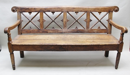 A 19TH CENTURY POSSIBLY SWEDISH PINE BENCH, with a decoratively carved and pierced back, having four X-centred panels beneath elongated moustache bar top, having twin downward turning arms, double planked solid seat, on turned and blocked forelegs with plain rear, 94cm high x 190cm widest point