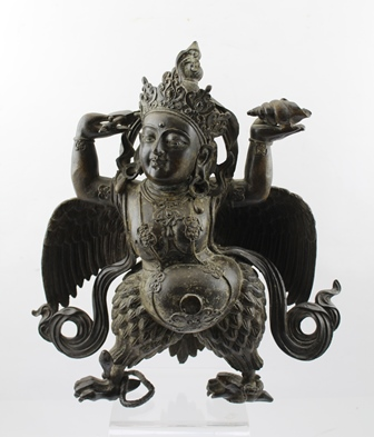 A LATE 19TH CENTURY TIBETAN BRONZE BUDDHISTIC TANTRIC WINGED GARUDA DEITY, crowned, bearing ritual objects in his hands, a conch shell and axe, 33cm high