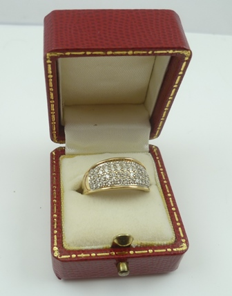AN 18CT GOLD AND DIAMOND DRESS RING, having fifty-four small diamonds set in a wide band, stamped 575, size N