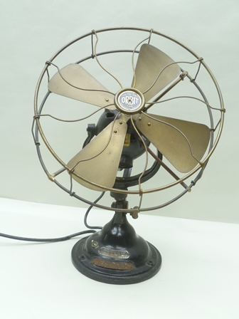 AN ORIGINAL VERITYS OF BIRMINGHAM 12 ORBIT TABLE/WALL MOUNTABLE ELECTRIC FAN, having brass blades and guard, on a black stove enamelled base with applied plaque with serial numbers, 53cm at its highest - this item has a unique and ingenious rotating action rather than the standard oscillation