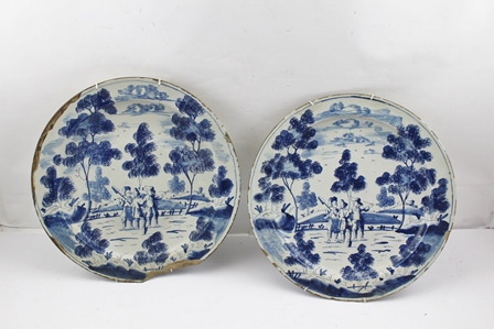 A PAIR OF 18TH CENTURY ENGLISH TIN GLAZED EARTHENWARE CHARGERS each painted in the Dutch manner with rural landscapes, workmen conversing in a field surrounded by trees and low hills, 33cm diameter