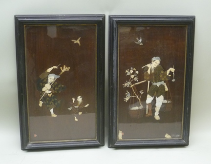 A PAIR OF JAPANESE MEIJI PERIOD SHIBAYAMA PANELS, grained hardwood inlaid with ivory, mother of pearl and lacquer, depicting figures and birds. The one with a peasant water carrier, the other a wanderer with staff and gourd chasing a boy, both with inlaid character seal marks, in ebonised glazed frames, 68cm x 39cm