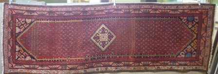 A LATE 20TH CENTURY WOVEN WOOLLEN FLOOR RUNNER, having central pole medallion on a busy field with triple deep guard borders, 102cm wide x 312cm long