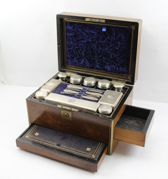 A LATE VICTORIAN ROSEWOOD TRAVELLING CASKET, brass mounted, opening to reveal silver plated mounted appointments, jars, boxes, manicure items etc., drawer to base has leather writing surface and jewellery storage below, 30cm wide