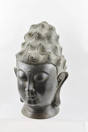 A LATE 19TH CENTURY CHINESE BRONZE BUDDHA HEAD, represented with wavy tight curled hair, half-closed eyes in a state of meditation, feint smile of serene nature and nobility having attained enlightenment, bears Uma between eyes, featuring elongated ear lobes, 35cm high