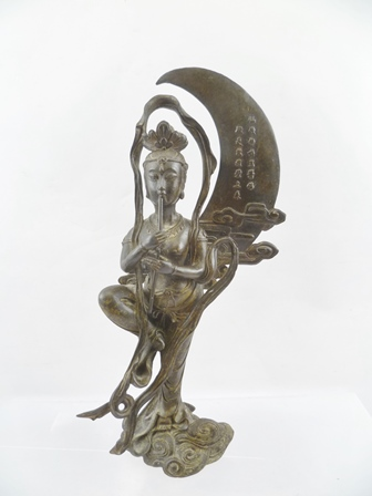 A 19TH CENTURY CHINESE BRONZE of Change, Goddess of The Moon, depicting standing on one leg with a flute before a crescent moon, bearing character script, 29.5cm high