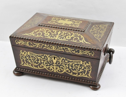 AN EARLY 19TH CENTURY REGENCY ROSEWOOD NEEDLEWORK BOX of sarcophagus shape, brass inlaid, with ring handles, raised on bun feet, opens to reveal decorative interior with removable tray, 30.5cm wide