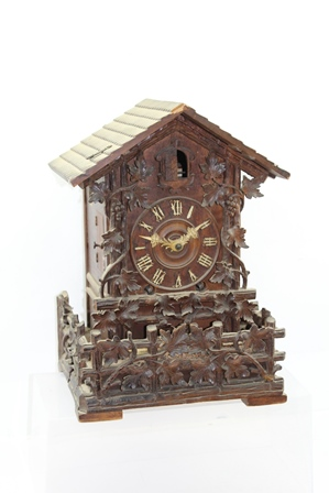 A BLACK FOREST CUCKOO CLOCK of architectural form, with carved fruiting vine decoration to the front and balcony, 26cm wide x 37cm high, together with a wall mounting BRACKET