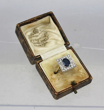 AN 18CT GOLD ART DECO DESIGN DRESS RING set central oval sapphire surrounded by diamonds in a square head, size N